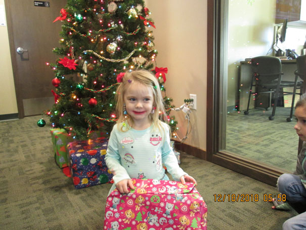 Little girl opening a christmas gift in front of a Christmas tree with a big smile on her face